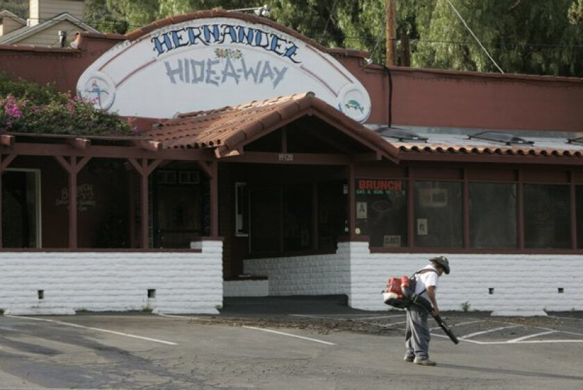 A gardener clears leafs from the parking lot in front of Hernandez Hideaway Restaurant in Escondido.