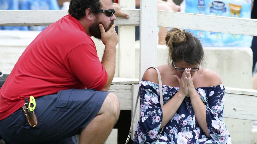 A woman prays outside the Santa Fe ISD Alamo Gym where students and faculty are being brought after