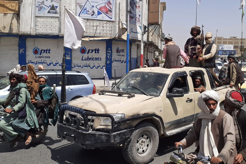 A pickup truck carrying fighters moves through traffic in Kandahar.