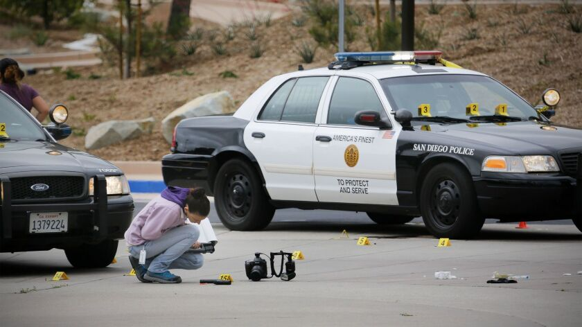 A member of the San Diego Police Department examines what appears to be a gun on the ground at the s