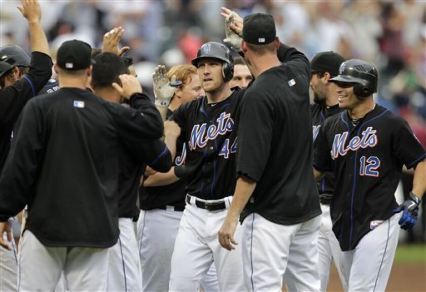 New York Mets' Jason Bay, center, is greeted by teammates after batting in the winning run during the tenth inning of an interleague baseball game against the New York Yankees, Sunday, July 3, 2011, at Citi Field in New York. The Mets defeated the Yankees 3-2. (AP Photo/Seth Wenig)