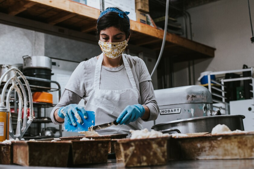 Owner/head baker Roanna Canete uses a mask while baking at her newly opened Gluten Free Baking Co. in North Park. It opened in February just as worries of the pandemic began sweeping through San Diego.