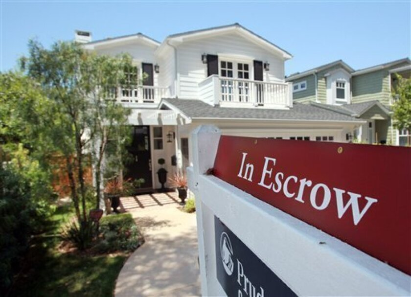 """In this June 23, 2009 photo, an """"in escrow"""" sign is seen on a home for sale in the Pacific Palisades area of Los Angeles. The National Association of Realtors said Wednesday, July 1, 2009, pending home sales rose in May for the fourth straight month, fresh evidence that the housing sector may be recovering. (AP Photo/Reed Saxon)"""