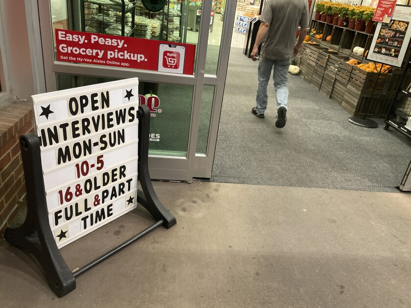 In this Thursday, Oct. 7, 2021, photograph, a sign for potential hires stands outside the door to a Hy-Vee grocery store in Sioux Falls, S.D. Companies that typically hire thousands of seasonal workers are heading into the holidays during one of the tightest job markets in decades, making it unlikely they'll find all the workers they need. For shoppers, it might mean a less than jolly holiday shopping experience, with bare store shelves and online orders that take longer than usual to fill. (AP Photo/David Zalubowski)