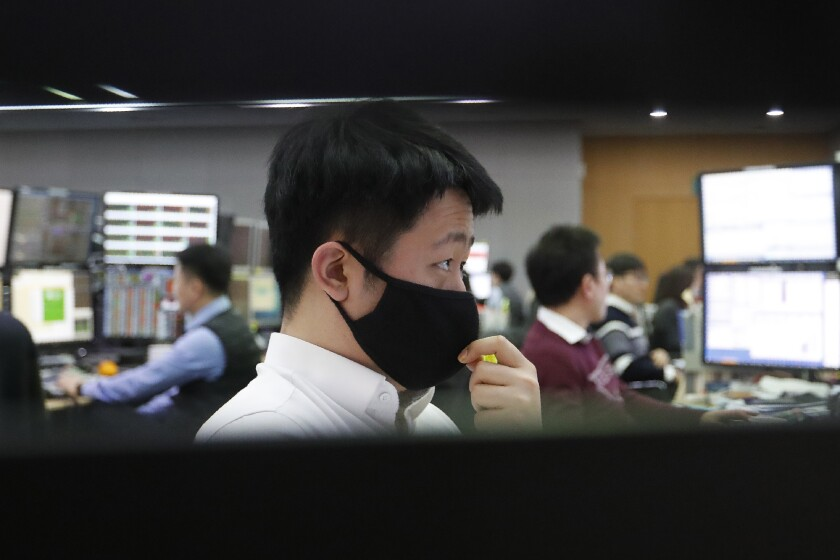A currency trader wearing a face mask watches monitors at the foreign exchange dealing room of the KEB Hana Bank headquarters in Seoul, South Korea, Thursday, March 5, 2020. Asian shares rose Thursday, taking their cue from a surge on Wall Street as governments and central banks took more aggressive measures to fight the virus outbreak and its effects on the economy.(AP Photo/Ahn Young-joon)