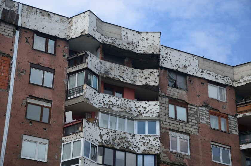 On many Sarajevo apartment buildings that were located near sniper positions in the siege of the early 1990s, scars from shelling remain, and sometimes makeshift window coverings as well.
