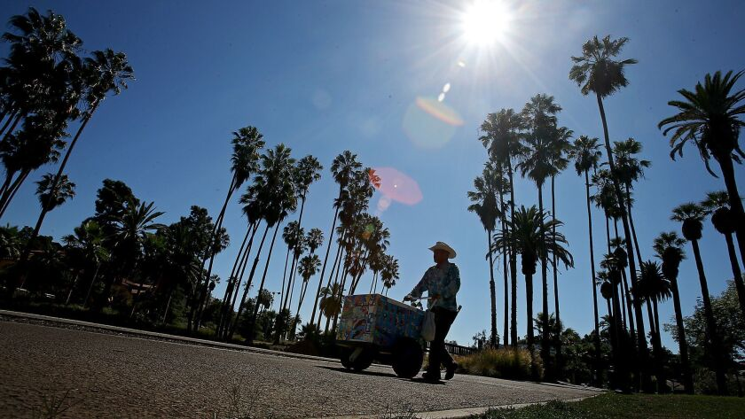 LOS ANGELES, CALIF. - SEP. 22, 2014. An ice cream vendor pushes a cart on the sidewalk that rings Ec