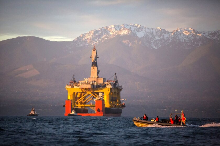 FILE - In this April 17, 2015 file photo, with the Olympic Mountains in the background, a small boat crosses in front of an oil drilling rig as it arrives in Port Angeles, Wash., aboard a transport ship after traveling across the Pacific. The Obama administration has given Royal Dutch Shell PLC approval to begin limited exploratory oil drilling off Alaska's northwest coast. The two permits issued Wednesday, July 22, 2015, clear the way for drilling in Chukchi Sea, but with conditions. (Daniella Beccaria/seattlepi.com via AP, File) MAGS OUT; NO SALES; SEATTLE TIMES OUT; TV OUT; MANDATORY CREDIT