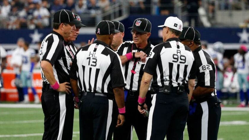 Head linesman Patrick Turner (13), referee Tony Corrente (99), field judge Buddy Horton (82) and other officials gather on the field during a game between the Bengals and the Cowboys on Oct. 9.