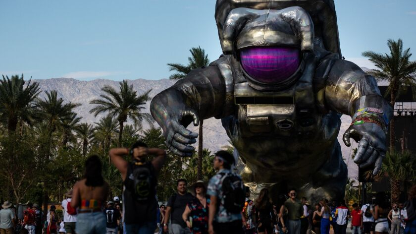 """INDIO, CALIF. - APRIL 19: People walk the festival grounds, with the """"Overview Effect"""" by Poetic Kin"""