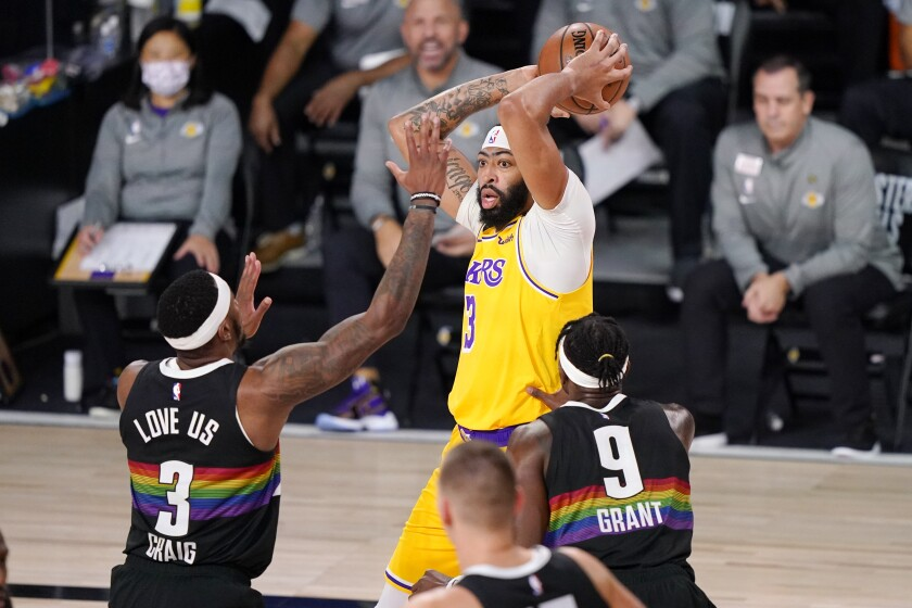 Lakers forward Anthony Davis looks to pass over Denver Nuggets forwards Torrey Craig and Jerami Grant.