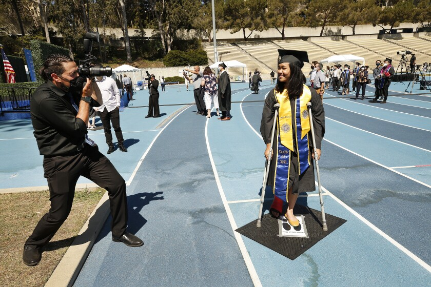 """LOS ANGELES, CA - JUNE 10: Sophia Bautista, 22, graduating with a degree in Political Science and Labor Studies is on crutches as she broke her foot in a skate boarding accident only days before as graduating UCLA students walk the stage in Drake Stadium while their names are announced with their image on a video monitor and pose for official photographs as they take part in a """"Graduation Celebration."""" Up to 230 students per hour will participate in the graduate procession through Drake Stadium each day for six days with up to one student every 15 seconds. More than 9,000 students over six days starting Thursday before and after a virtual ceremony on Friday night, will walk through Drake Stadium with up to two guests to get the graduation experience of crossing a real stage as their names are read. Roughly 14,000 undergraduates and graduate students total are expected to receive their degrees from UCLA this year. UCLA on Thursday, June 10, 2021 in Los Angeles, CA. (Al Seib / Los Angeles Times)."""