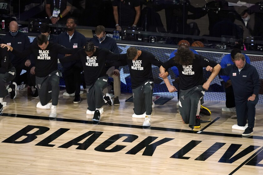 Members of the Bucks join arms as they kneel during the national anthem before Game 5 against the Magic on Aug. 29, 2020.