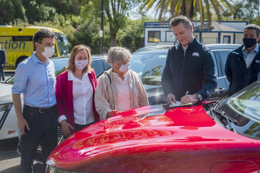 On the hood of an electric car, California Gov. Gavin Newsom signs an executive order on climate change.