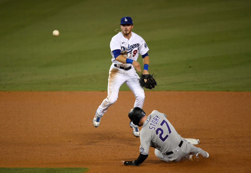 Dodgers second baseman Gavin Lux avoids a sliding Trevor Story as he throws to first base Sept. 4, 2020.