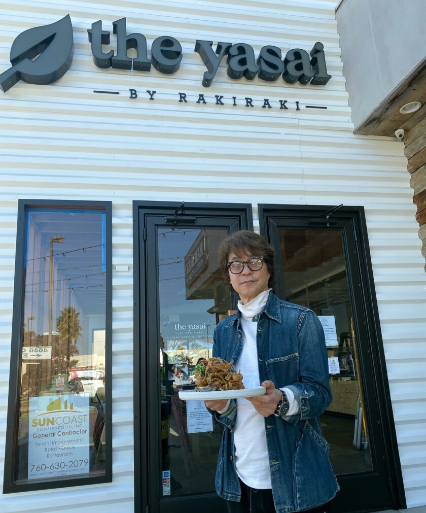 Chef/owner Junya Watanabe stands outside his new restaurant, The Yasai, with one of his favorite vegan dishes, crispy gobo, an onion strings-style tower of fried shavigns of burdock root sprinkled with nori dust and truffle zest.