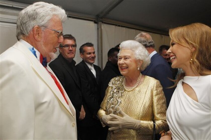 FILE - Queen Elizabeth II meets Rolf Harris and Kylie Minogue backstage at The Diamond Jubilee Concert in London in this Monday June 4, 2012 file photo . Harris, a veteran entertainer who has released hit singles and painted Queen Elizabeth II's portrait, has been arrested as part of a police investigation into sexual abuse allegations stemming from the Jimmy Savile scandal, British media reported Friday April 19 2013. (AP Photo / Dave Thompson, Pool)