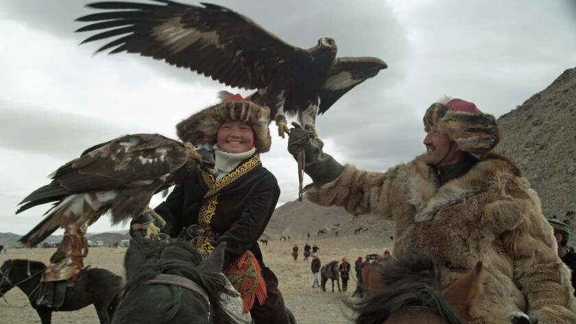 """Aisholpan and her father, Nurgaiv, in the documentary """"The Eagle Huntress."""""""
