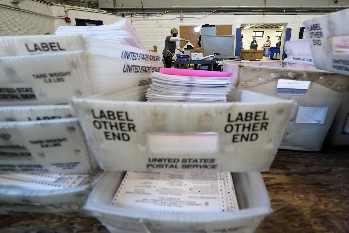 Chester County election workers scan mail-in and absentee ballots .