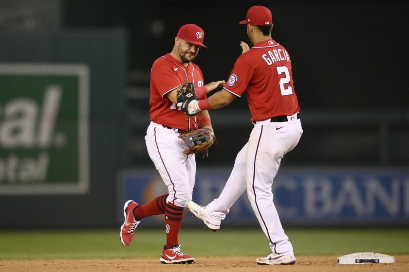 Kyle Schwarber (izquierda) y Luis García de los Nacionales de Washington celebran tras el segundo juego de la doble cartelera contra los Mets de Nueva York, el sábado 19 de junio de 2021, en Washington. (AP Foto/Nick Wass)