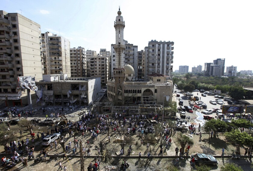 FILE - In this Friday, Aug. 23, 2013 file photo, people gather outside the al-Salam Mosque amid charred cars and wide damage at the site of a car bombing, which killed dozens, in the northern city of Tripoli, Lebanon. A Lebanese court has sentenced Friday, Nov. 1, 2019 a man to death in a 2013 twin car bombs in the northern city of Tripoli that killed 47 people. (AP Photo/Bilal Hussein, File)