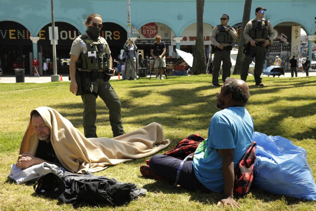 A sheriff's deputy talks to a homeless men sitting on grass.