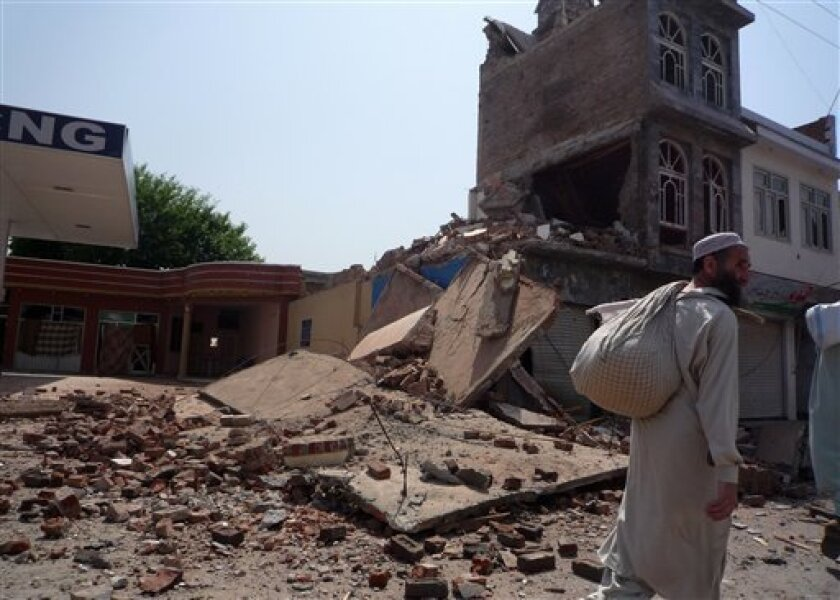 A Pakistani walks past the destruction caused by fighting between Pakistani security forces and Taliban militants in Mingora, the main town of Pakistan's troubled Swat Valley, Sunday, May 31, 2009.  Pakistan says it is close to beating the Taliban in the Swat Valley, but battlefield success alone d