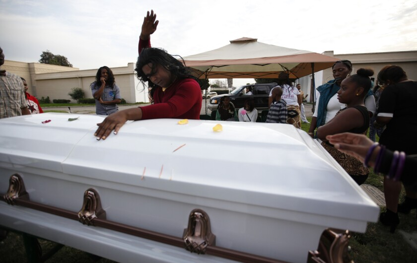 Mourner Paulisha Thomas dances in tribute to Deshwanda Sanchez before her burial at Angeles Abby Memorial Park in Compton on Dec. 19.