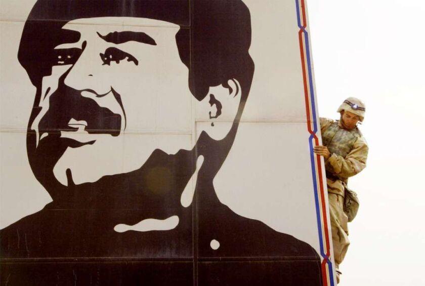 A U.S. Marine prepares to pull down a billboard of Iraqi ruler Saddam Hussein in  2003.