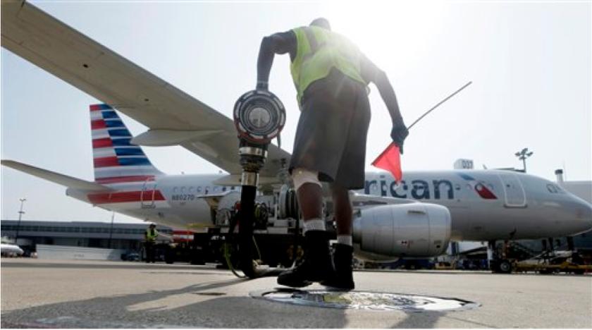 Scott Mills carga combustible en un avión de American Airlines en Grapevine, Texas. La industria areonáutica se ha ahorrado miles de millones de dólares con la abrupta baja de los precios del petróleo. La industria energética, en cambio, se ha visto obligada a despedir mucha gente y a reducir costos. La baja en los precios del petróleo se hace sentir a nivel mundial y nada hace pensar que se puede producir un alza en los precios en un futuro cercano. (AP Photo/LM Otero, File)