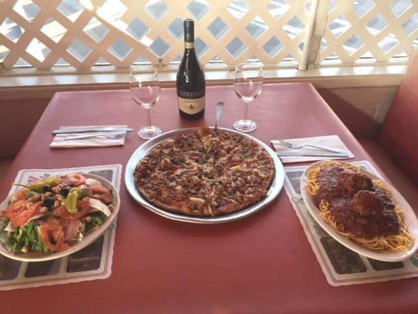 A table is set with some classic Italian dishes: Antipasto Salad, Handlebar Pizza and Spaghetti with Meatballs at Pernicano's Family Restaurant in Pacific Beach.