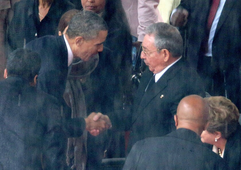 President Obama, left, shakes hands with Cuban President Raul Castro during the official memorial service for former South African President Nelson Mandela at FNB Stadium in Johannesburg.
