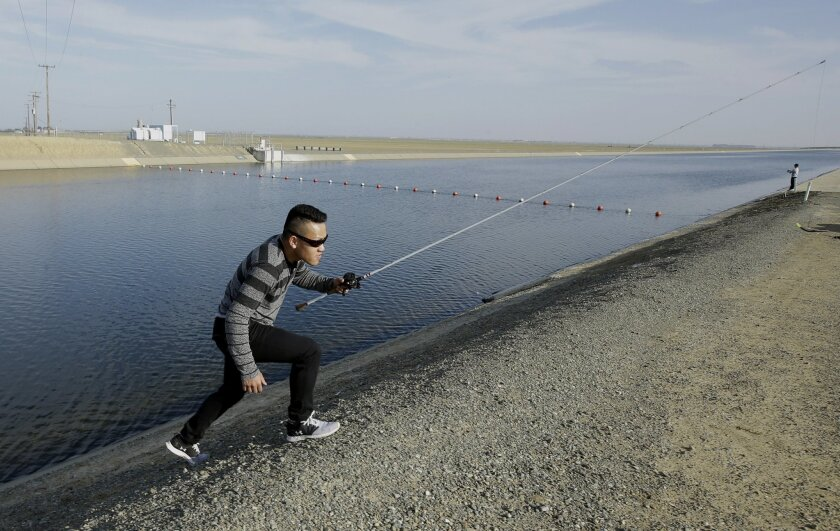 In this Thursday, Feb. 25, 2016 photo, Sha Xinog, climbs the bank to get more bait while fishing along the California Aquaduct near Firebaugh, Calif. The over 400-mile long aqueduct ships water from rivers and reservoirs in Northern California to Central Valley farmers and water users in Southern C