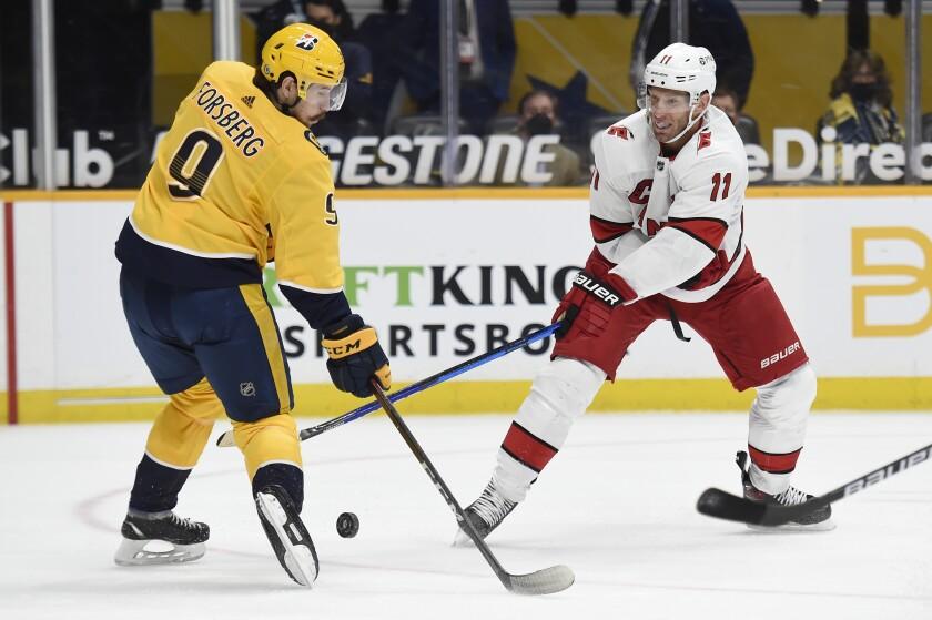 Nashville Predators left wing Filip Forsberg (9) blocks a shot by Carolina Hurricanes center Jordan Staal (11) during the first period of an NHL hockey game Saturday, May 8, 2021, in Nashville, Tenn. (AP Photo/Mark Zaleski)