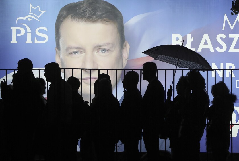 In this photo taken Thursday Sept. 26, 2019 supporters of Poland's ruling right-wing party are standing in line before a candidate's billboard to get to a party convention in Warsaw, Poland, ahead of Sunday parliamentary election in which the Law and Justice party is hoping to win a second term in power. (AP Photo/Czarek Sokolowski)