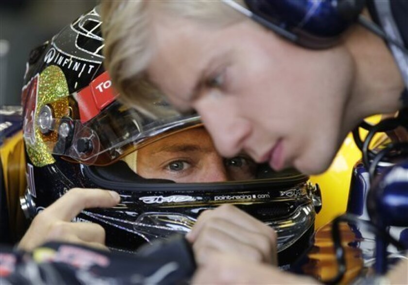Red Bull Formula One driver Sebastian Vettel of Germany talks to a team mechanic as he waits to start in the third practice session for the Singapore Formula One Grand Prix on the Marina Bay City Circuit in Singapore, Saturday, Sept. 22, 2012. (AP Photo/Mark Baker)