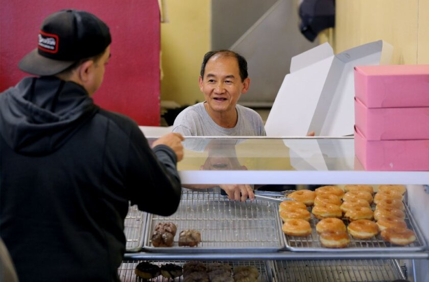 Chow's Donuts owner Bernard Simieng, at right, fills a doughnut order for customer Frank Alvarez on Friday.