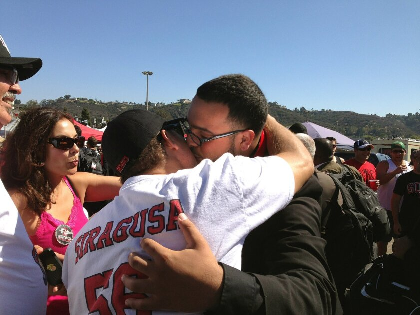 San Diego, Ca.-- Nico Siragusa (right), hugs his father, Ramon, as he heads into Qualcomm Stadium before the Oregon State game against SDSU as his mother, Diane (left) and uncle Russ Sanchez (far left) watch. Photo by Stephanie Loh/UT San Diego.