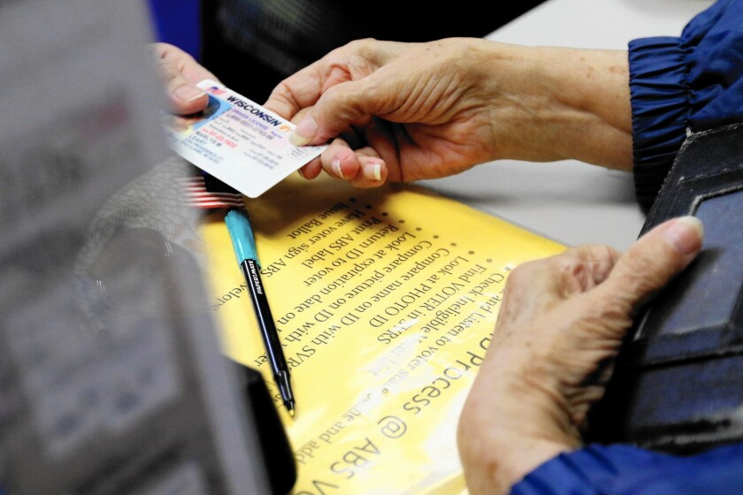 A woman hands her photo identification card to an election assistant in Eau Claire, Wis. on March 21.