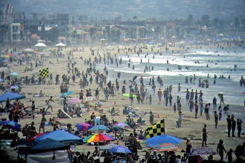 People dotted the sands of Pacific Beach, photographed through binoculars at the lifeguard station.  (K.C. Alfred / U-T)