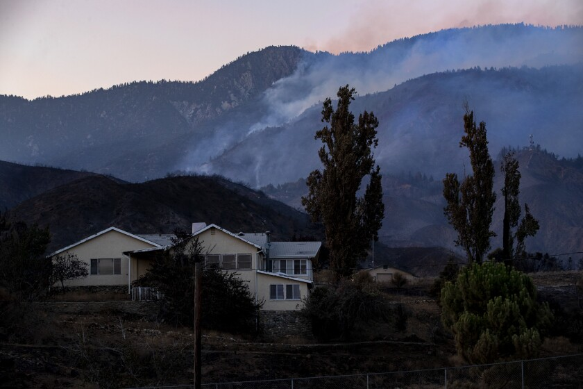 Scorched terrain surrounds a home off Bluff Street in Banning, Calif., as the Apple fire smolders Tuesday.