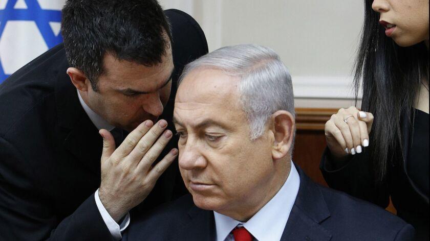 Spokesman David Keyes, left, leans in to speak to Israeli Prime Minister Benjamin Netanyahu in a July meeting of the Cabinet in his Jerusalem office.