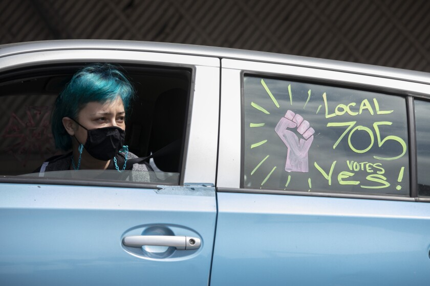 """A woman wearing a face mask in the drivers seat of a car. The backseat window says """"Local 705 votes yes!"""""""