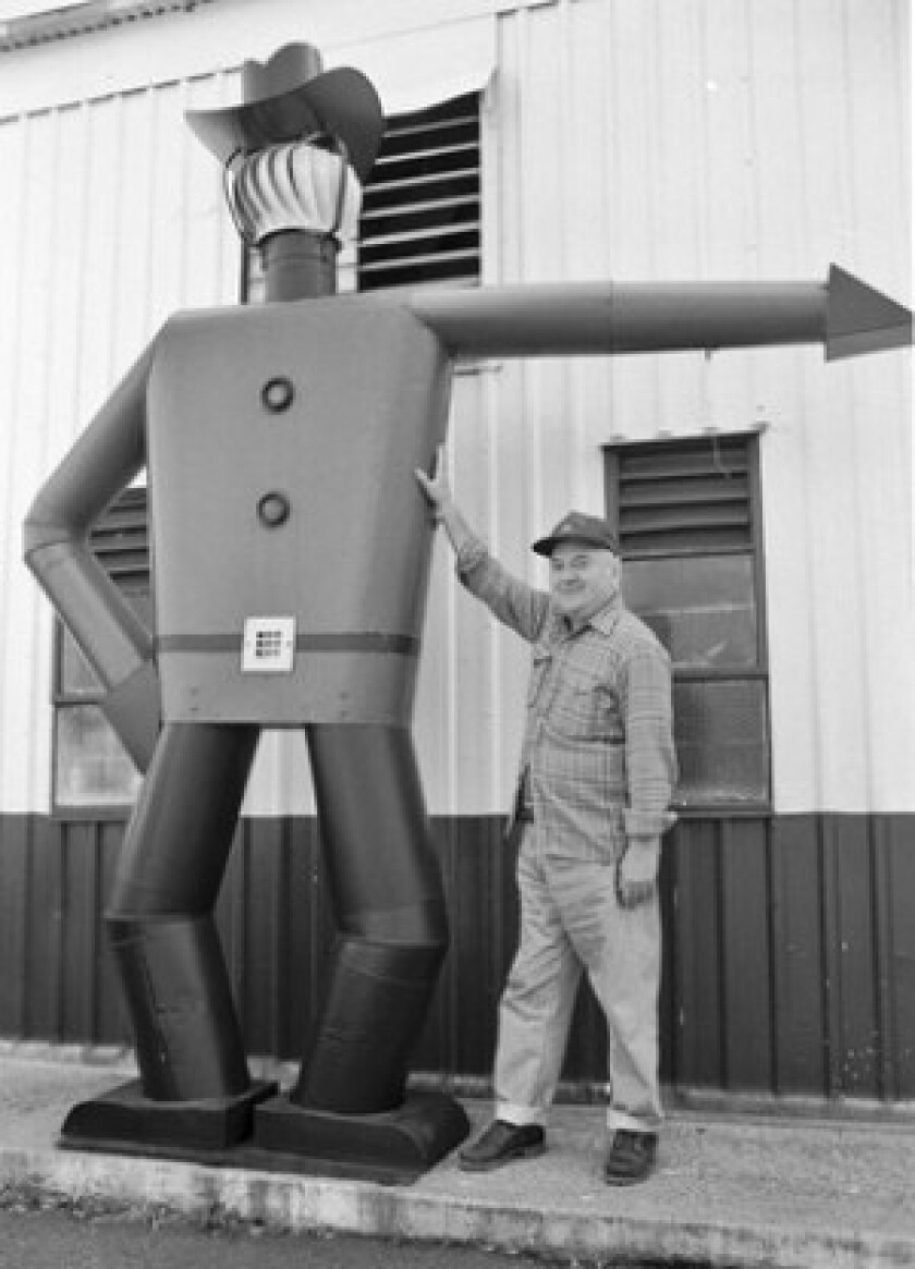 "Archie Green poses with Mr. Dixie, an 11-foot-tall ""Tin Man"" sculpture at the Dixie Sheet Metal Works in Falls Church, Va. His book ""Tin Men"" was published in 2002."