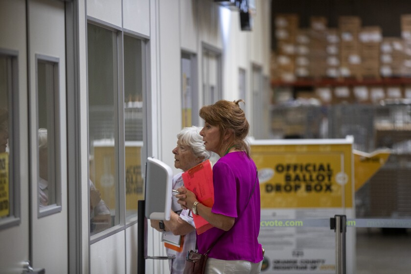 Two women election watchers look through a window where ballots are being processed.