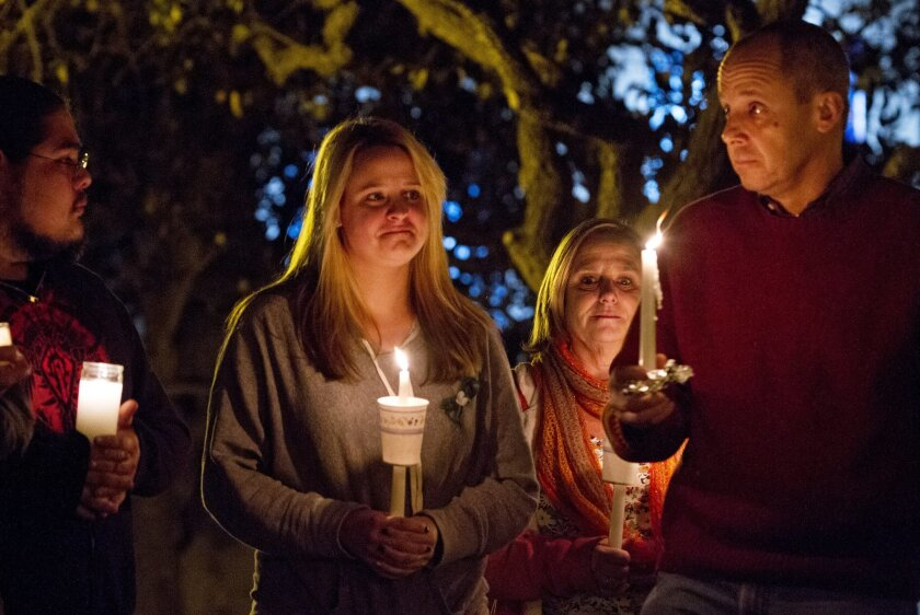 Kerin Sovern, center, who is from Sandy Hook, Connecticut, but now lives in San Diego, attends a candlelight vigil honoring victims of the Sandy Hook Elementary School in Connecticut at Balboa Park Thursday with her parents Maureen and Michael Sovern who are visiting her from Sandy Hook.