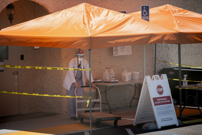 Healthcare workers work July 9 outside the Reo Vista Healthcare Center in San Diego.