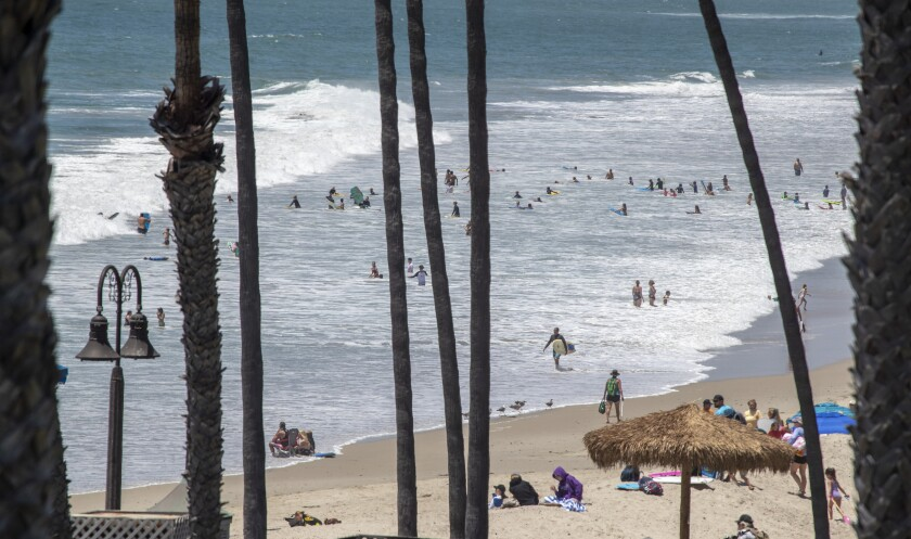 Beachgoers take to the water at the San Clemente Pier