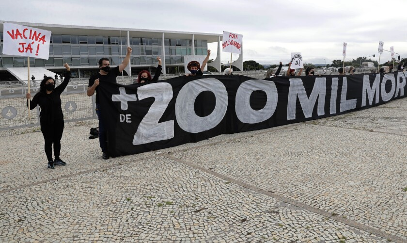 """Protesters shout slogans """"Vaccine now"""" and hold the Portuguese message """"Over 200,000 deaths. It's your fault, Bolsonaro,"""" referring to Brazilian President Jair Bolsonaro and the COVID-29 pandemic, outside the presidential palace in Brasilia, Brazil, Friday, Jan. 8, 2021, the day after Brazil passed 200,000 pandemic deaths. (AP Photo/Eraldo Peres)"""