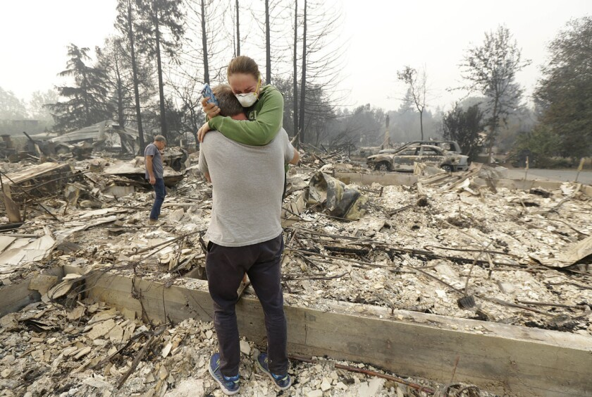 On Oct. 10, 2017, Todd Caughey hugs his daughter Ella as they visit the site of their home destroyed by fires in Kenwood, Calif. (Jeff Chiu/AP)